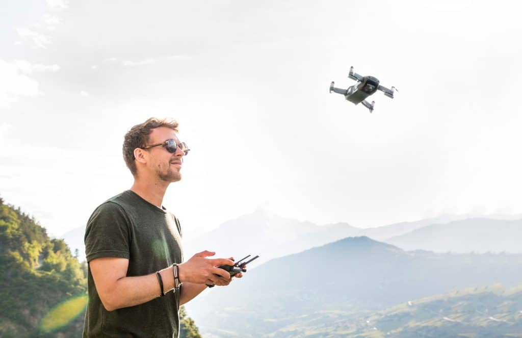 A mountain view with a man controlling his drone